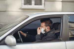 serious man in disposable mask and earbuds driving car at daytime